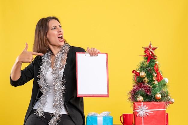 Weihnachtsstimmung mit emotionaler schöner dame, die im büro steht und dokumente im büro auf gelb zeigt