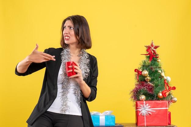 Weihnachtsstimmung mit emotionaler schöner dame, die im büro steht und rote tasse im büro auf gelb hält