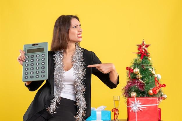 Weihnachtsstimmung mit emotionaler schöner dame, die im büro steht und taschenrechner im büro auf gelb zeigt