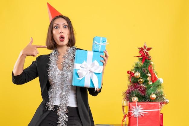 Weihnachtsstimmung mit emotionaler schöner dame mit weihnachtshut, der geschenke im büro auf gelb zeigt