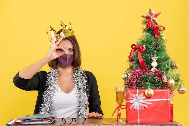 Weihnachtsstimmung mit ernsthafter schöner dame im anzug mit medizinischer maske und tragender maske, die spektakuläre geste im büro auf gelb macht