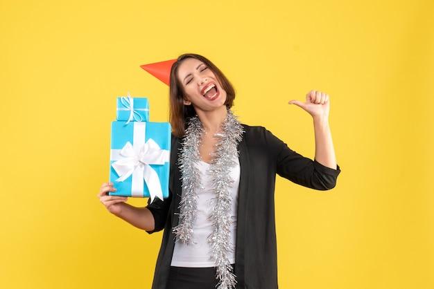 Weihnachtsstimmung mit glücklicher emotionaler schöner dame mit weihnachtshut, der geschenke auf gelb hält