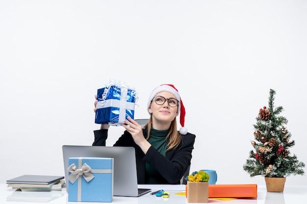Weihnachtsstimmung mit glücklicher junger frau mit weihnachtsmannhut und tragen von brillen, die an einem tisch sitzen, der ihr geschenk überraschend auf weißem hintergrund hält