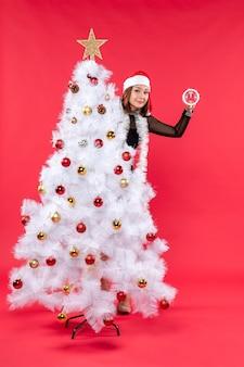 Weihnachtsstimmung mit glücklicher schöner dame in einem schwarzen kleid mit weihnachtsmannhut, der sich hinter neujahrsbaum versteckt
