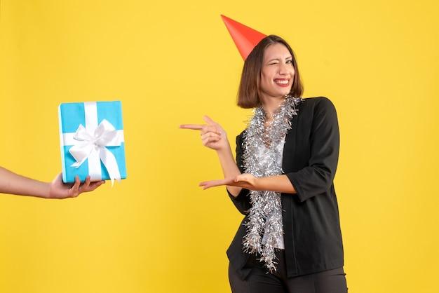 Weihnachtsstimmung mit glücklicher und aufgeregter geschäftsdame im anzug mit weihnachtsmütze, die das handhaltende geschenk auf gelb zeigt