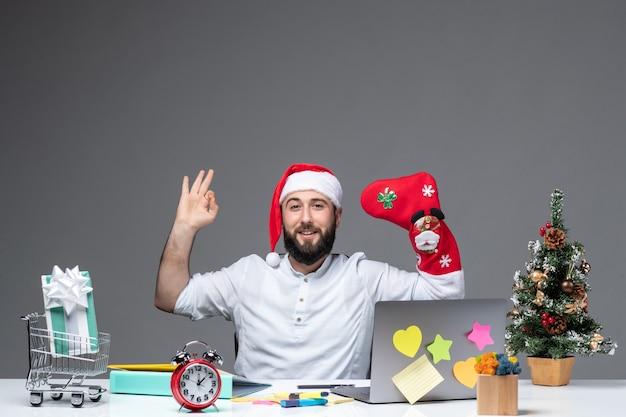 Weihnachtsstimmung mit jungem erwachsenen mit weihnachtsmannhut und tragen weihnachtssocke zu seiner hand, die ok geste im büro auf weißem hintergrund macht