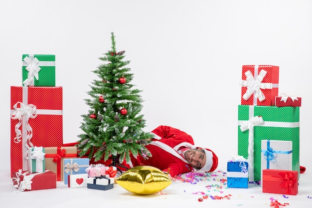 Weihnachtsstimmung mit jungem lustigem glücklichem weihnachtsmann, der hinter weihnachtsbaum nahe geschenken in verschiedenen farben auf weißem hintergrund liegt