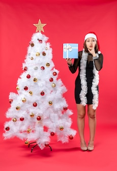 Weihnachtsstimmung mit jungem mädchen in einem schwarzen kleid mit weihnachtsmannhut, der nahe weihnachtsbaum steht, der neujahrsgeschenk hält und jemanden anruft