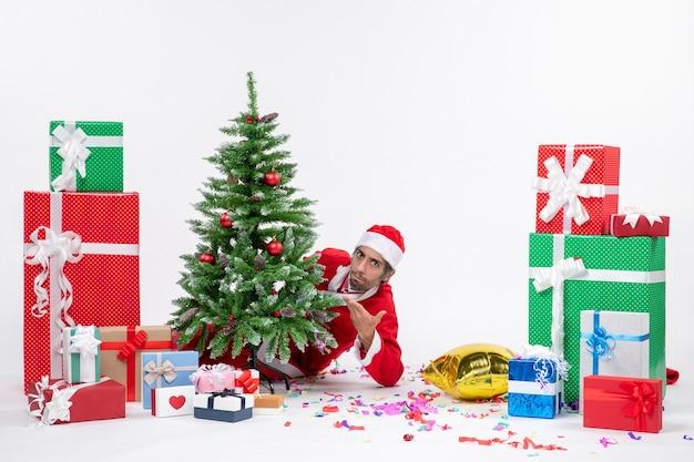 Weihnachtsstimmung mit jungem weihnachtsmann, der sich hinter weihnachtsbaum nahe geschenken in verschiedenen farben auf weißem hintergrundmaterial versteckt