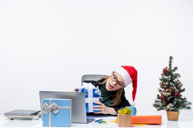 Weihnachtsstimmung mit junger frau mit weihnachtsmannhut und tragen von brillen, die an einem tisch sitzen und ihr geschenk überraschend auf weißem hintergrund betrachten