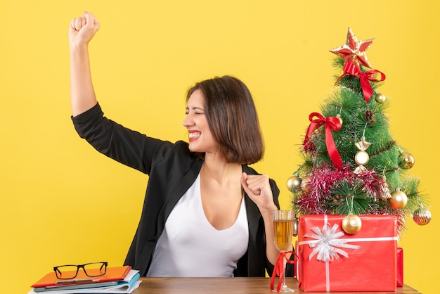 Weihnachtsstimmung mit junger geschäftsdame, die ihren erfolg stolz auf gelb genießt