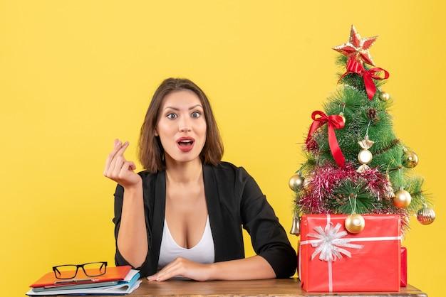Weihnachtsstimmung mit junger konzentrierter schöner frau, die geldgeste macht und im büro sitzt