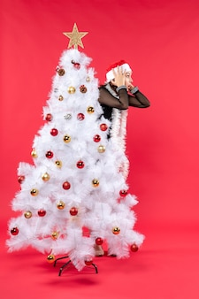 Weihnachtsstimmung mit junger schockierter schöner dame in einem schwarzen kleid mit weihnachtsmannhut, der sich hinter neujahrsbaum versteckt