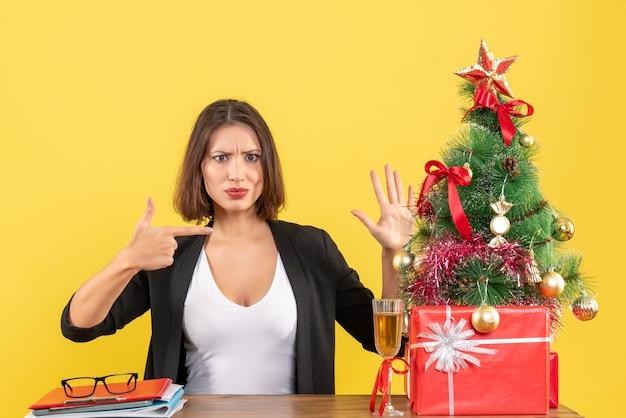 Weihnachtsstimmung mit junger unbefriedigter ernsthafter emotionaler geschäftsdame, die ihre hand auf gelb zeigt