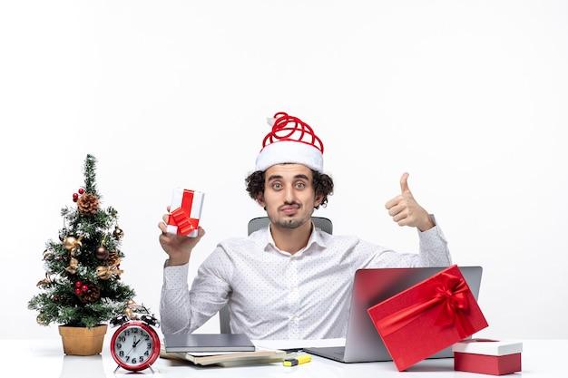 Weihnachtsstimmung mit lächelndem stolzem jungen geschäftsmann mit weihnachtsmannhut und halten seines geschenks, das oben auf weißem hintergrund zeigt