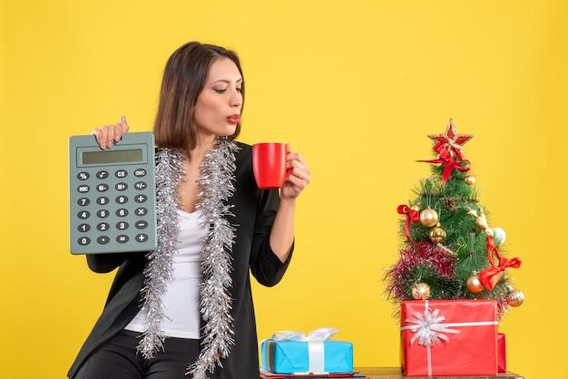 Weihnachtsstimmung mit lächelnder schöner dame, die im büro steht und rechnerbecher im büro auf gelb hält
