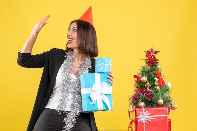 Weihnachtsstimmung mit lächelnder schöner dame mit weihnachtshut, der geschenke hält, die im büro auf gelb begrüßen