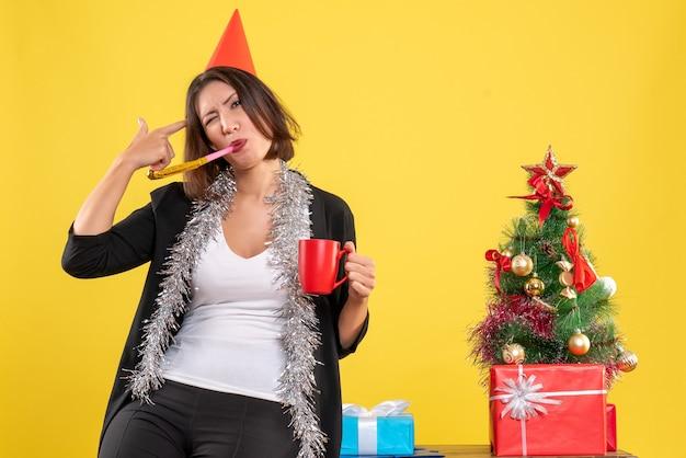 Weihnachtsstimmung mit lustiger schöner dame, die die rote tasse im büro auf gelb hält