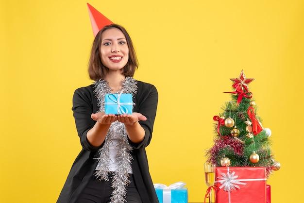 Weihnachtsstimmung mit positiver schöner dame, die geschenk glücklich im büro auf gelb hält