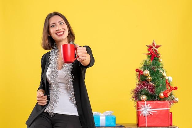 Weihnachtsstimmung mit positiver schöner dame, die im büro steht und rote tasse im büro auf gelb hält