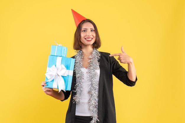 Weihnachtsstimmung mit positiver schöner dame mit weihnachtshut, der geschenke auf gelb zeigt