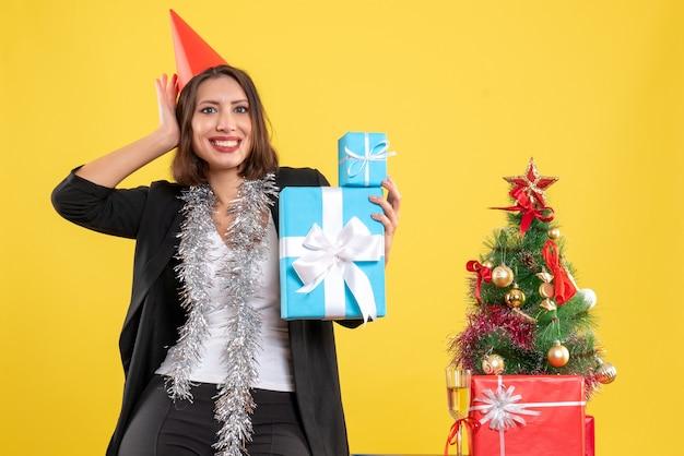 Weihnachtsstimmung mit positiver schöner dame mit weihnachtshut, der geschenke im büro auf gelb hält