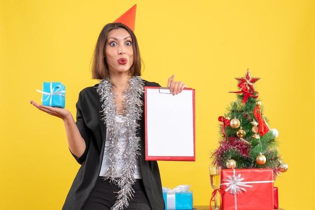 Weihnachtsstimmung mit schockierter schöner dame, die dokument und geschenk im büro auf gelb hält