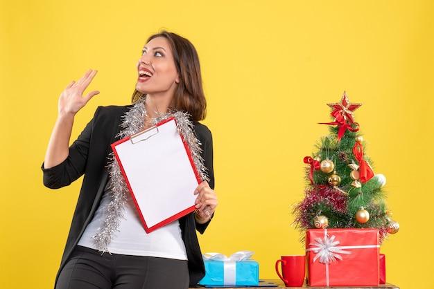 Weihnachtsstimmung mit schockierter schöner dame, die im büro steht und dokumente im büro auf gelb hält