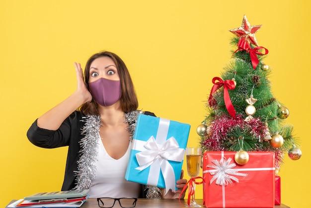 Weihnachtsstimmung mit schockierter schöner dame im anzug mit medizinischer maske und haltegeschenk im büro
