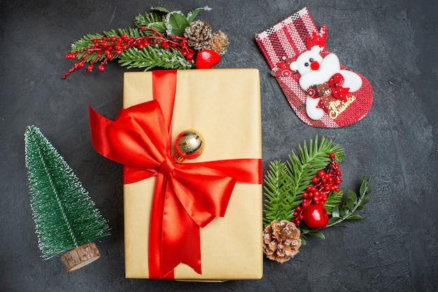 Weihnachtsstimmung mit schönen geschenken mit bogenförmigem band und tannenzweigdekorationszubehörweihnachtssocke auf einem dunklen tisch