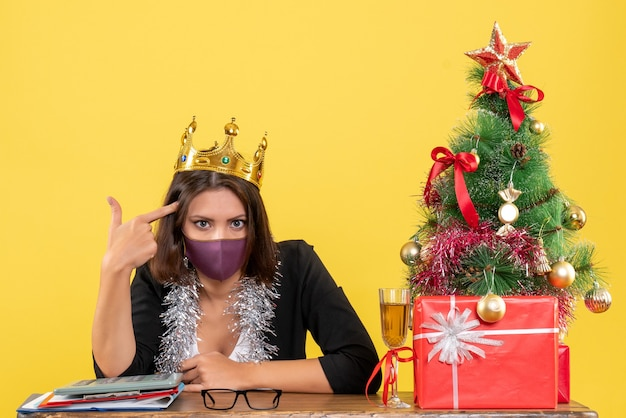 Weihnachtsstimmung mit schöner dame im anzug mit krone, die ihre medizinische maske im büro auf gelb trägt