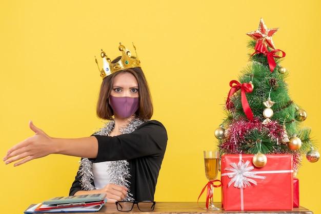 Weihnachtsstimmung mit schöner dame im anzug mit medizinischer maske und tragender maske, die jemanden im büro auf gelb begrüßt
