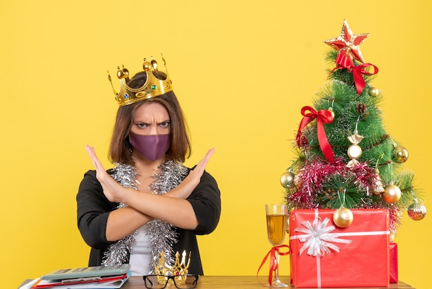 Weihnachtsstimmung mit schöner dame im anzug mit medizinischer maske und tragender maske, die negative geste im büro auf gelb macht