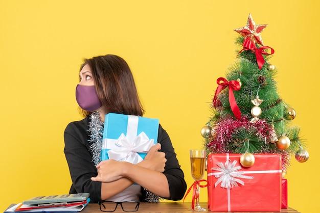 Weihnachtsstimmung mit schöner dame im anzug mit medizinischer maske und umarmungsgeschenk im büro auf gelb