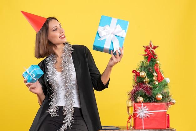 Weihnachtsstimmung mit schöner dame mit weihnachtshut, die geschenk glücklich im büro auf gelb hält Kostenlose Fotos