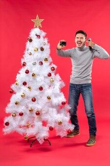 Weihnachtsstimmung mit stolzem kerl, der nahe geschmücktem weihnachtsbaum steht und mikrofon und telefon hält, das sein ohr schließt