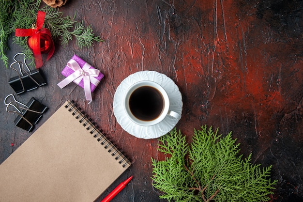 Weihnachtsstimmung mit tannenzweigen dekozubehör und geschenk neben notizbuch mit stift auf dunklem hintergrund