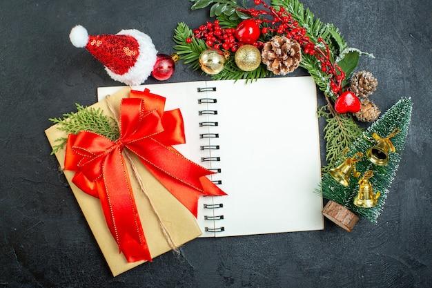 Weihnachtsstimmung mit tannenzweigen santa claus hut weihnachtsbaum rotes band auf notizbuch auf dunklem hintergrund