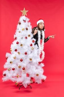 Weihnachtsstimmung mit überraschtem schönem mädchen in einem schwarzen kleid mit weihnachtsmannhut, der sich hinter neujahrsbaumfoto versteckt