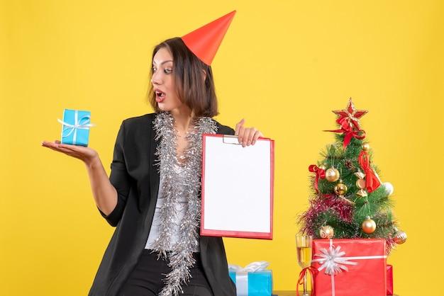 Weihnachtsstimmung mit überraschter schöner dame, die dokument und geschenk im büro auf gelb hält