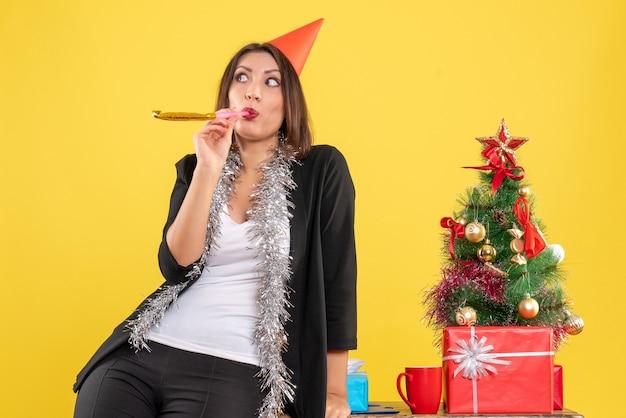 Weihnachtsstimmung mit überraschter schöner dame, die für kamera im büro auf gelb aufwirft