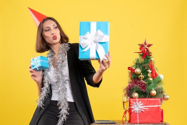 Weihnachtsstimmung mit überraschter schöner dame mit weihnachtshut, der geschenk glücklich im büro auf gelb hält