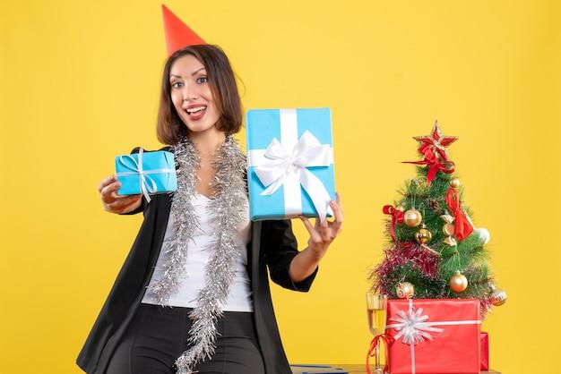 Weihnachtsstimmung mit überraschter schöner dame mit weihnachtshut, der geschenke glücklich im büro auf gelb zeigt