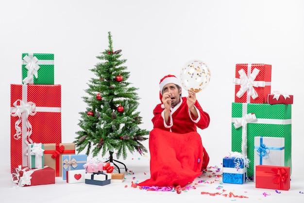 Weihnachtsstimmung mit verängstigtem weihnachtsmann, der ballon hält, der nahe weihnachtsbaum und geschenke in verschiedenen farben auf weißem hintergrund sitzt