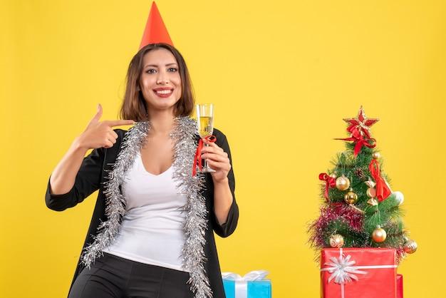 Weihnachtsstimmung mit verwirrter schöner dame, die wein im büro auf gelb hält und zeigt