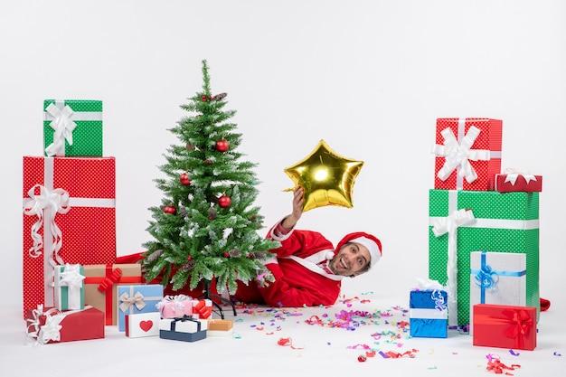 Weihnachtsstimmung mit weihnachtsmann, der hinter weihnachtsbaum nahe geschenken in verschiedenen farben auf weißem hintergrund liegt