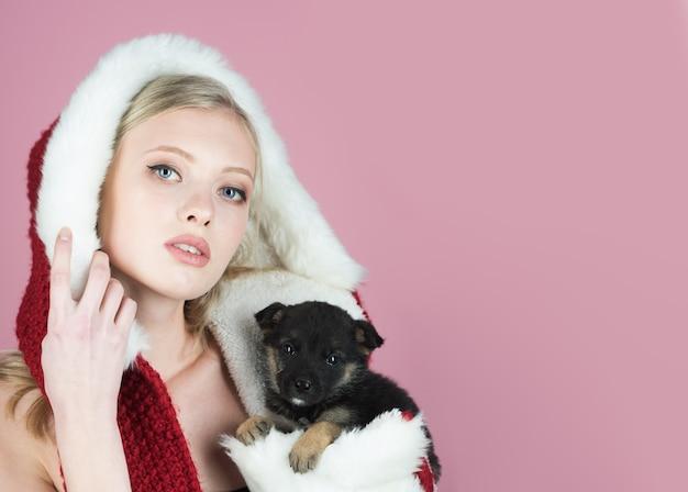 Weihnachtsstimmung schöne junge frau im weihnachtsmann-hut mit ihrer welpenpartyfeier und
