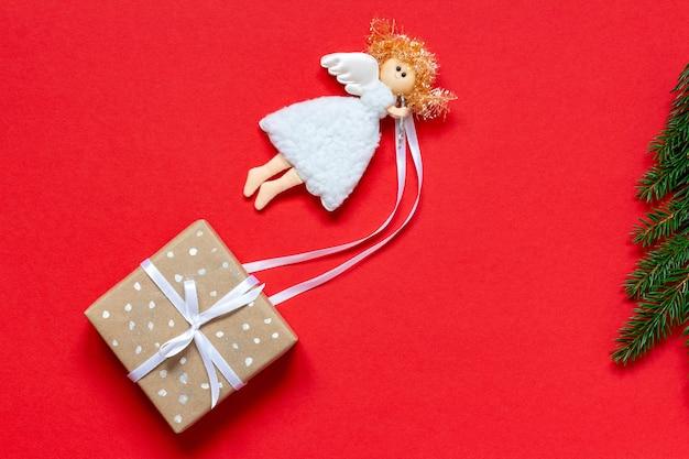 Weihnachtsstimmung trägt ein geschenk in öko-verpackung zum fichtenbaum