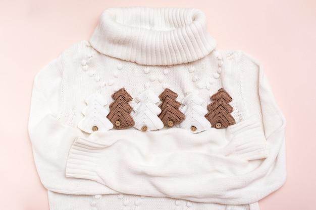 Weihnachtsstimmung. weißer pullover umarmt gestrickte tannen. handwerksdekor. kein verlust
