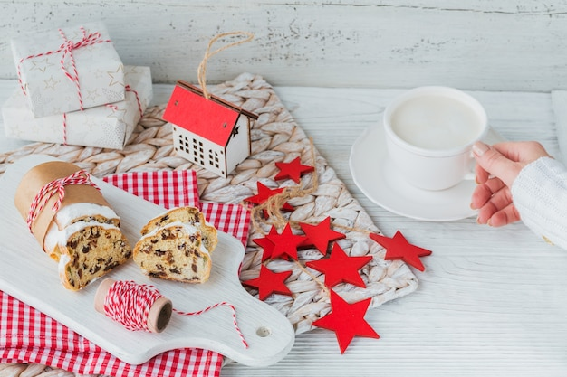 Weihnachtsstollen auf einem weißen holztisch geschnitten. stollen zu weihnachten. weibliche hand im warmen pullover, der tasse kaffee hält